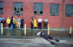 August 2003.  New Orleans, Louisiana, USA..Homicide detectives and body baggers converge on a bloody scene in the 6th district, New Orleans. The body of Lamont Mitchell lies in the dirt where he was dragged from a battered Buick Regal just hours earlier. Mitchell was shot and killed for little more than poking fun at men he considered friends. Colleague James Bannister was arrested a day later for the murder of Lamont Mitchell. Bannister was later convicted of 2nd degree murder. .Photo credit; Charlie Varley.