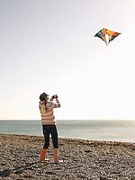 Pre teen girl flying kite on beach full length