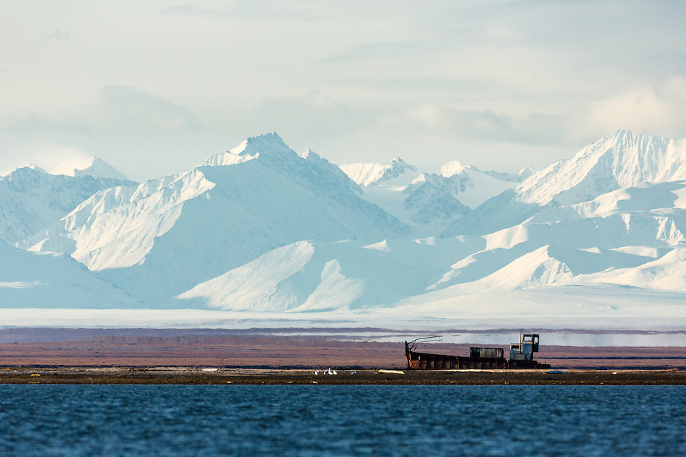 The Brooks Range looms large over a shipwrecked boat off Barter Island near Kaktovik in the Arctic National Wildlife Refuge in the Far North of Alaska. Autumn. Morning.