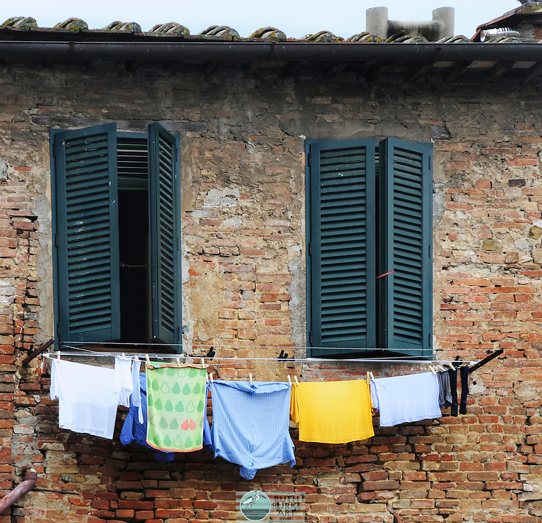 Windows with green shutters and hanging clothes on a stone building in Sienna,Italy.