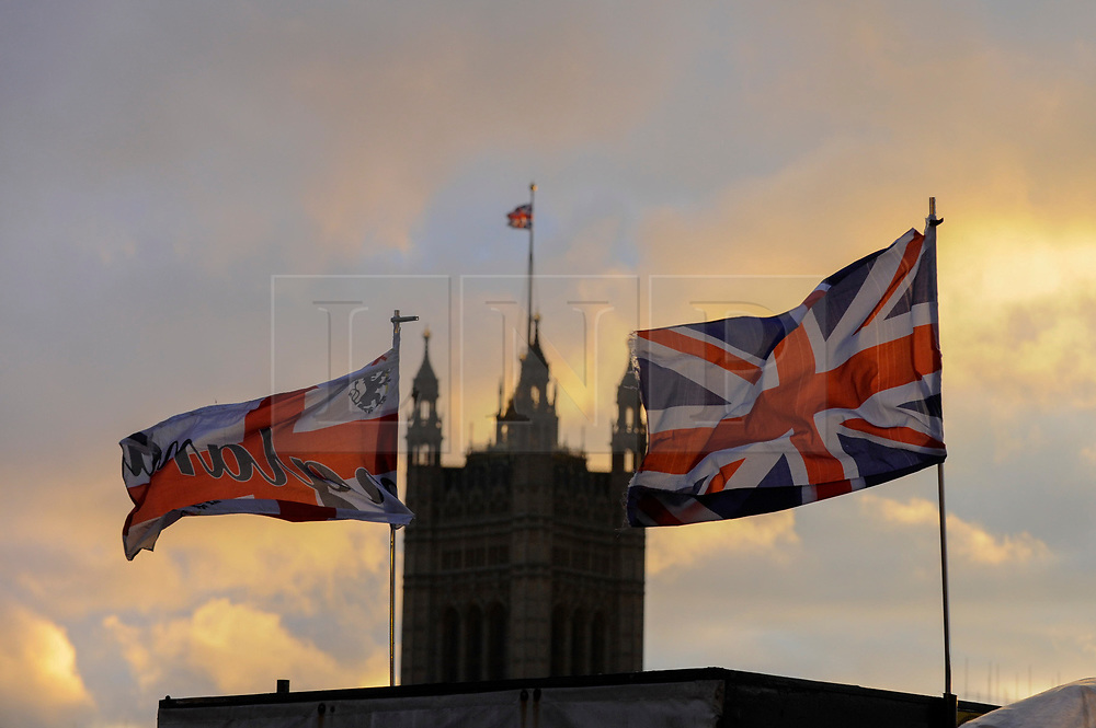 © Licensed to London News Pictures. 21/03/2017. London, UK. A Cross of St George flag and Union Jack flag blow in the wind a the sun sets behind The Houses of Parliament in Westminster, on the day of the Spring Equinox and the day that Theresa May, Prime Minister, announced that 29 March would be the day that the UK would trigger Article 50 to exit the European Union. Photo credit : Stephen Chung/LNP