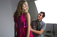 Designer adjusting fashion model's dress in studio