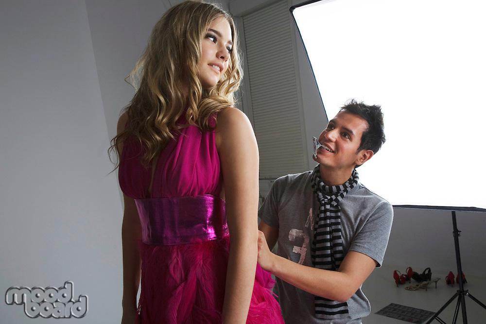 Designer adjusting fashion model's dress in studio