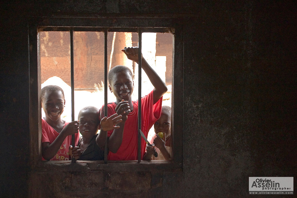 Group of children peeking through window in small village near Swedru.