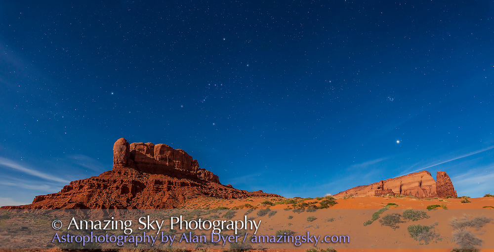A panorama of the winter sky setting in the evening over the Tear Drop Arch Mesa at Monument Valley, Utah on April 3, 2015. Illumination is from the Full Moon, about to be eclipsed in a few hours at dawn. At left is Sirius and Canis Major, at left of centre is Orion, at right of centre is Taurus and at right is the Pleiades and Venus. This is a two-panel stitch of exposures with the 24mm lens and Canon 6D, each 15 seconds at f/3.5 at ISO 800, untracked.