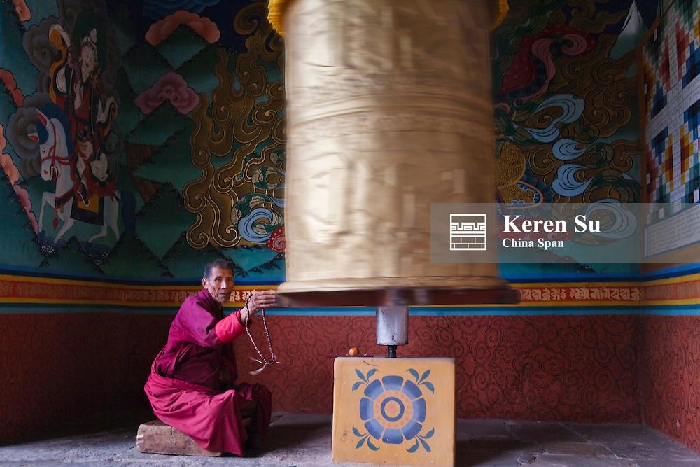 Monk pushing praying wheel, Punakha Dzong, Bhutan