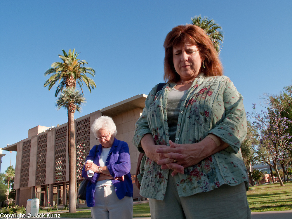 07 MAY 2009 -- PHOENIX, AZ: Olive Garrett (CQ) from Phoenix, LEFT and January Knuth (CQ) from Tempe, pray during the National Day or Prayer services at the State Capitol in Phoenix Thursday. About 30 people came to the capitol to pray for government officials at the desks of legislators.  Photo by Jack Kurtz