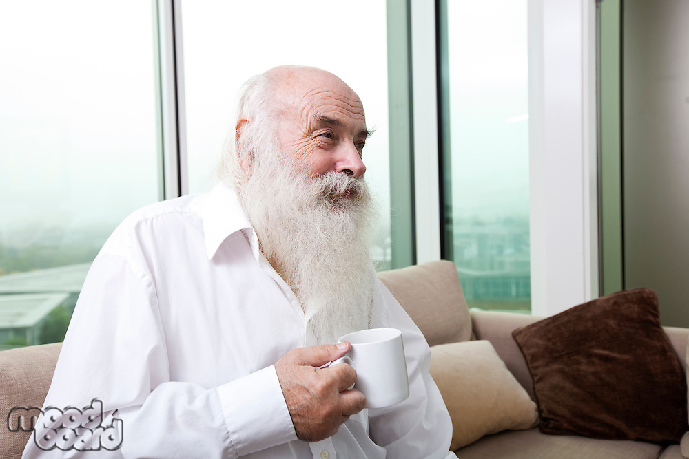 Senior man holding coffee cup at home
