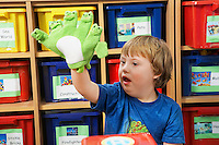 Boy (5-6) with Down syndrome playing with finger puppets in kindergarten
