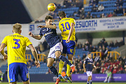 Millwall midfielder Ryan Leonard (28) in the air with Birmingham City forward Lukas Jutkiewicz (10)  during the EFL Sky Bet Championship match between Millwall and Birmingham City at The Den, London, England on 28 November 2018.
