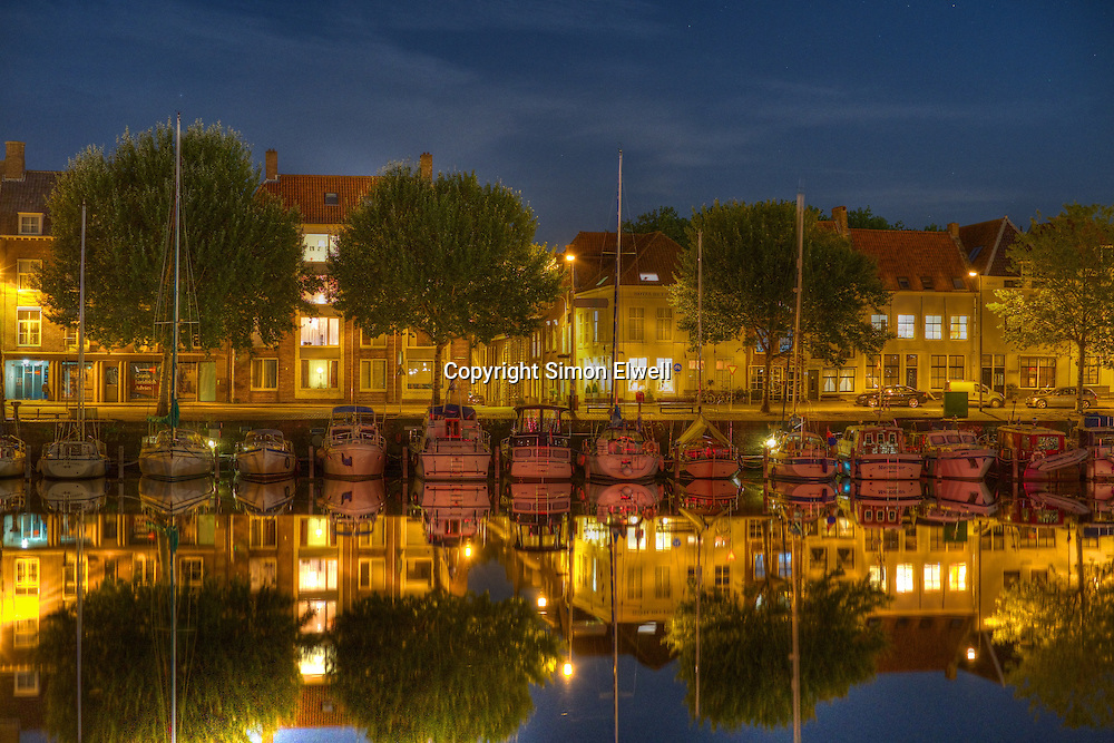Boats, trees and houses are reflected in the water at Middelburg, Holland