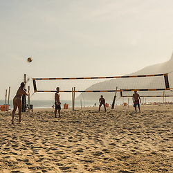 People playing football on Ipanema beach at sunset, Rio de Janeiro, Brazil.