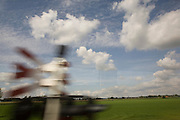 View of southern Holland through the passenger train window. Puffy white clouds, green fields and blurred level crossing warning, dipicting motion