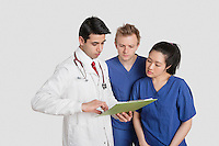 Three healthcare professional discussing medical report over gray background