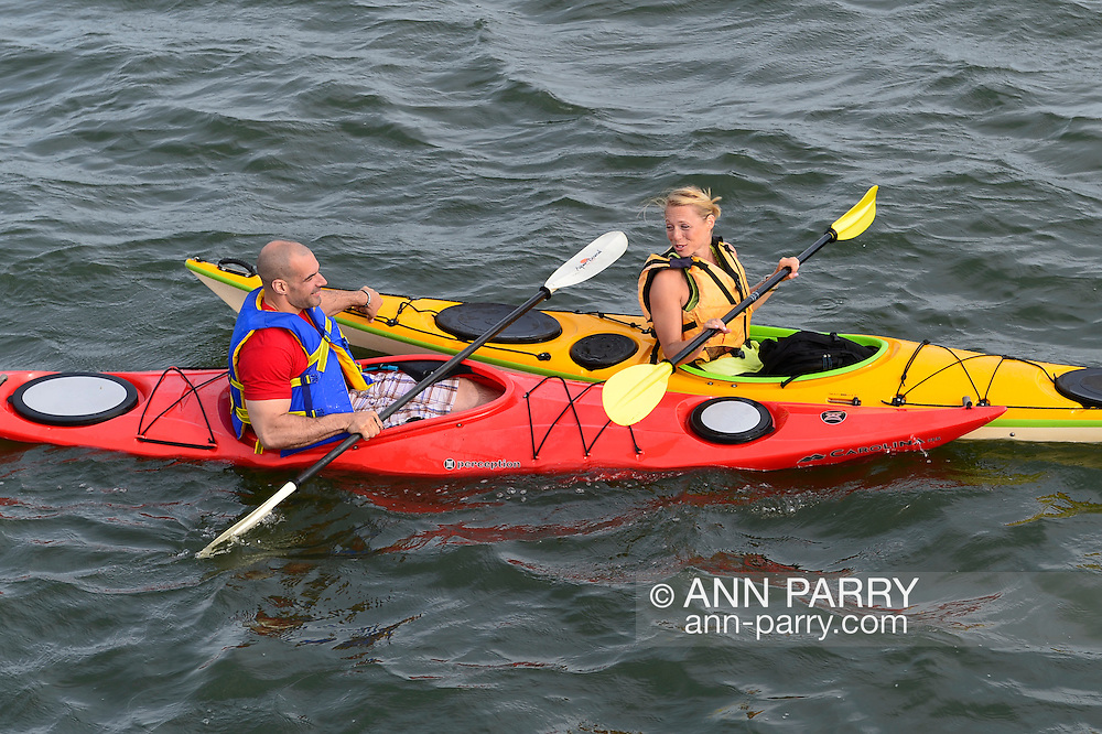 A young man and woman are kayaking in Merrick Bay along the south shore of Levy Park & Preserve during the Memorial Day Weekend. The red kayak had Carolina and the yellow kayak had Montauk written on their bows.