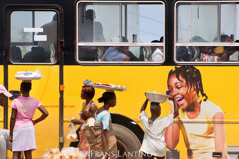 Street vendors and ad for cell phone company on bus, Accra, Ghana