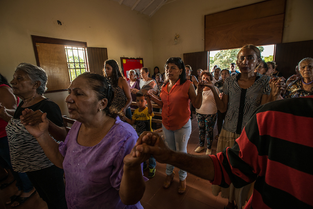 "LA VELA, VENEZUELA - SEPTEMBER 12, 2016: Florangel Amaya de Ramos (center) attends mass to pray for her missing son, Jesús Ramos who disappeared after leaving with a smuggler and other migrants to travel illegally and look for work in Curaçao. Jesús knew he would have to swim ashore from the smuggler's boat. So he spent his last weeks in Venezuela doing laps in the sea in front of his home in La Vela, his mother recalls. But the boat carrying the men never made it - it vanished somewhere off the coast of Venezuela last year. No wreckage was found. The only evidence that their journey even occurred is a few selfies sent from their smartphones just before they departed. The men posed on the side of the skiff with big smiles. ""I try not to cry — I tell myself, 'he's well, that's it,'"" said Ms. Ramos. Questions haunt the families of the lost migrants each time they look out toward the sea. Could the men still be alive somehow? Are these journeys worth it? Will Venezuela ever return to the country that it was, one where it was not necessary to swim to the shore in Curaçao after being tossed from a fishing boat? Ms. Ramos is still waiting for her son and speaks of him in the present tense. Each Monday, she goes to Mass to pray for his return.""I always speak to God,"" said Ms. Ramos. ""I am always looking up at that picture of the Virgin. I am scared one day she will yell back at me, 'Enough, already. That's enough.'"" PHOTO: Meridith Kohut for The New York Times"
