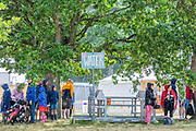 Henham Park, Suffolk, 20 July 2019. The rain falls and people dash for cover oddly hiding under a tree at a water station - The 2019 Latitude Festival.