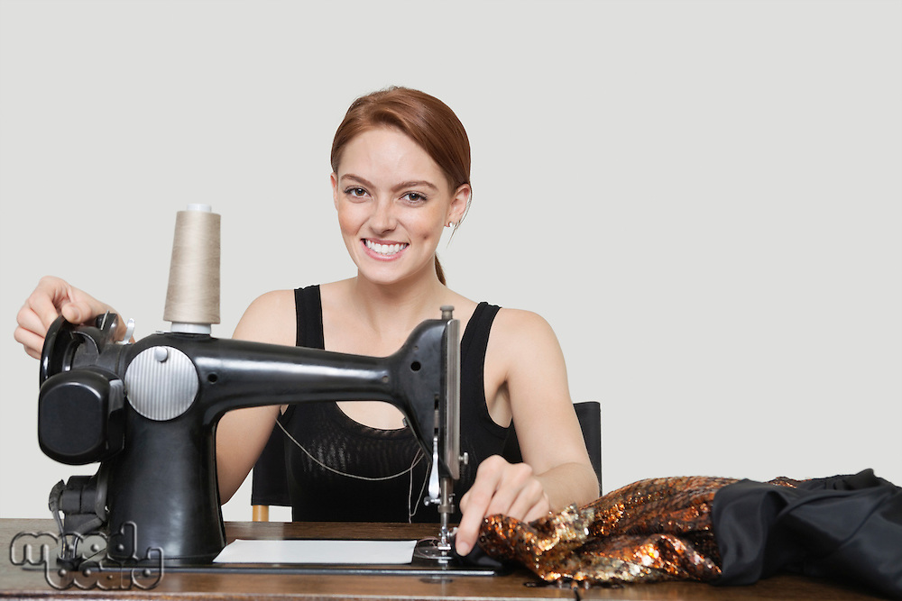 Portrait of young female tailor stitching cloth on sewing machine over colored background