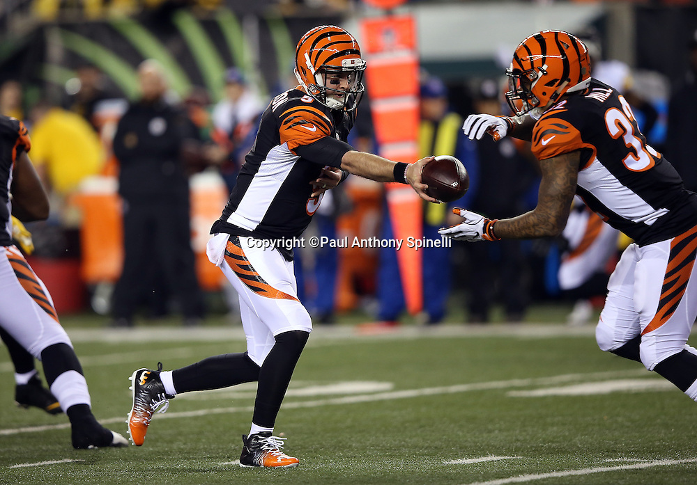 Cincinnati Bengals quarterback AJ McCarron (5) hands off the ball to Cincinnati Bengals running back Jeremy Hill (32) on a first quarter run during the NFL AFC Wild Card playoff football game against the Pittsburgh Steelers on Saturday, Jan. 9, 2016 in Cincinnati. The Steelers won the game 18-16. (©Paul Anthony Spinelli)