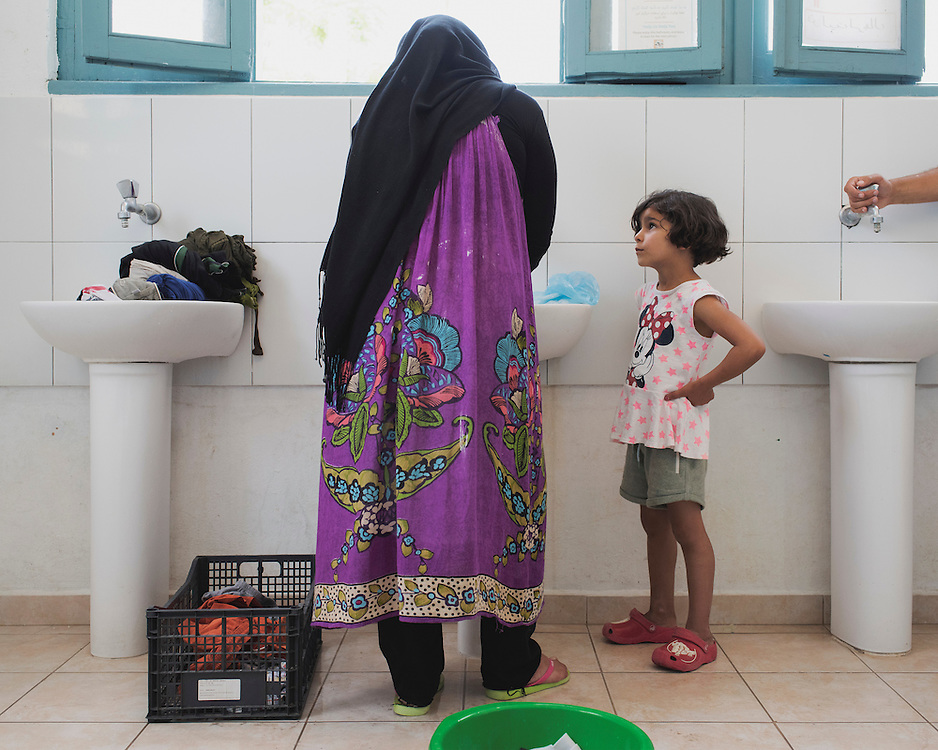 Kinaz looks at eight month pregnant Fadwa doing laundry in a bathroom at PIKPA, a refuge opened in January 2016 by the Leros Solidarity Network as a shelter for families and unaccompanied minors.