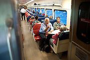 Republican candidate for U.S. Senate Chris Shays, front, left, and wife Betsi, talk with passenger Lou Forte, front right, of Guilford on a train in Madison, Conn. (AP Photo/Jessica Hill)