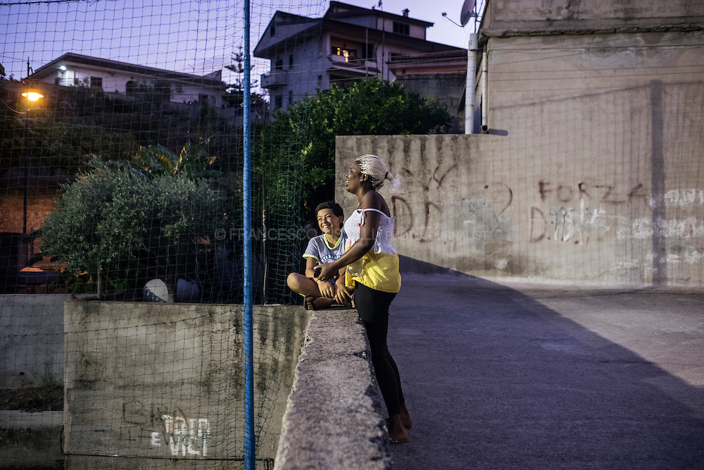A Nigerian woman is joking with a local kid at dusk. RIACE (ITALY) 01/08/16