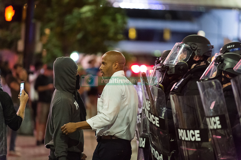 September 21, 2016 - Charlotte, North Carolina, United States of America - Sept. 21, 2016 - Charlotte, UNITED North CarolinaS - , A clergyman speaks with a protestor as police look on during a protest and eventual riot in Uptown Charlotte, North Carolina, The United States, Wednesday 21 September 2016. This is the second day of violence that erupted after a police officer's fatal shooting of an African-American man Tuesday afternoon. (Credit Image: © Sean Meyers via ZUMA Wire)