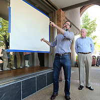 Chandler Griffin, with Blue Magnolia Films, stands with Gerald Wages, as he talks about the photos being unveilied at Reed's and all of downtown Tupelo on Thursday morning. The photo's also include a QR code that plays a video. Each participant used an iPhone 7 Plus and was tasked with choosing an aspect of the community and telling its story.