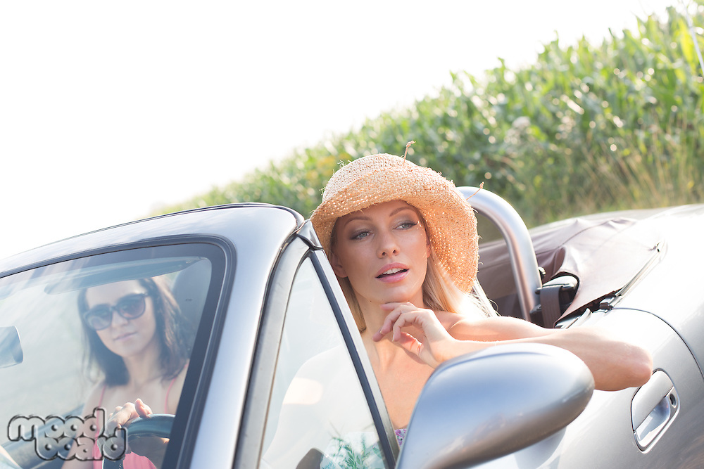 Female friends sitting in convertible on sunny day