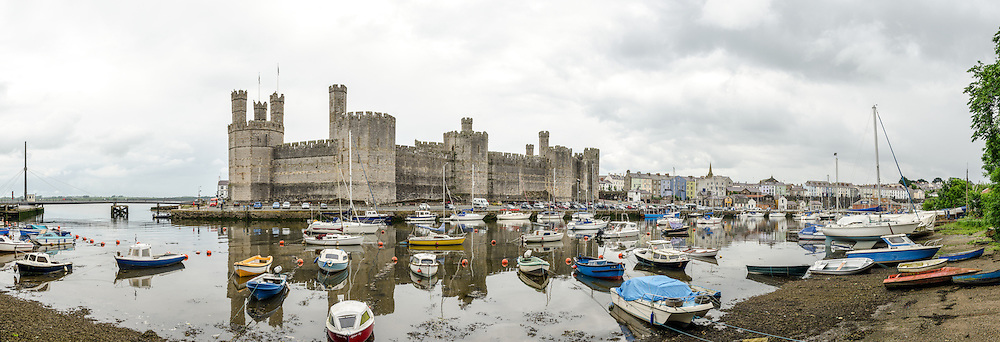 Panorama of exterior of Caernarfon Castle in northwest Wales. A castle originally stood on the site dating back to the late 11th century, but in the late 13th century King Edward I commissioned a new structure that stands to this day. It has distinctive towers and is one of the best preserved of the series of castles Edward I commissioned.