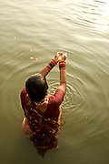 A woman makes an offering to the rising sun while standing in the Ganga River in Varanasi, India. It looks as though she holds the sun in her hands.