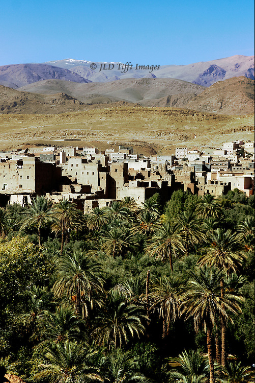 General view showing, in the foreground, agricultural land of planted fields, orchards, palm trees; in the middle distance, a mud brick village, with mosque minaret; in the distance, bare hills rising toward the Atlas Mountains.