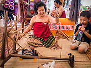 19 APRIl 2014 - BANGKOK, THAILAND: A woman shows a boy how to use a traditional spinning wheel at the Rattanakosin Festival in Bangkok. Rattanakosin is the name of the man made island that is the heart of the old city. Bangkok was formally founded as the capital of Siam (now Thailand) on 21 April 1782 by King Rama I, founder of the Chakri Dynasty. Bhumibol Adulyadej, the current King of Thailand, is Rama IX, the ninth King of the Chakri Dynasty. The Thai Ministry of Culture organized the Rattanakosin Festival on Sanam Luang, the royal parade ground in the heart of the old part of Bangkok, to celebrate the city's 232nd anniversary.    PHOTO BY JACK KURTZ