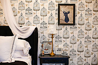 birdcage wallpaper invites you into the Reserve suite at Chateau Bourbon Luxury B&B.