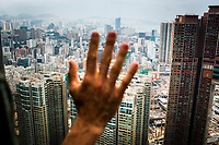 A man's hand on a glass window with the cityscape of Hong Kong and Kowloon beyond.