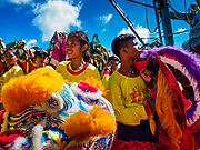 "02 JUNE 2017 - SAMUT SAKHON, THAILAND:  Children in a Lion dance troupe prepare to get off a boat after the procession on the Tha Chin River in Samut Sakhon. The Chaopho Lak Mueang Procession (City Pillar Shrine Procession) is a religious festival that takes place in June in front of city hall in Samut Sakhon. The ""Chaopho Lak Mueang"" is  placed on a fishing boat and taken across the Tha Chin River from Talat Maha Chai to Tha Chalom in the area of Wat Suwannaram and then paraded through the community before returning to the temple in Samut Sakhon. Samut Sakhon is always known by its historic name of Mahachai.     PHOTO BY JACK KURTZ"