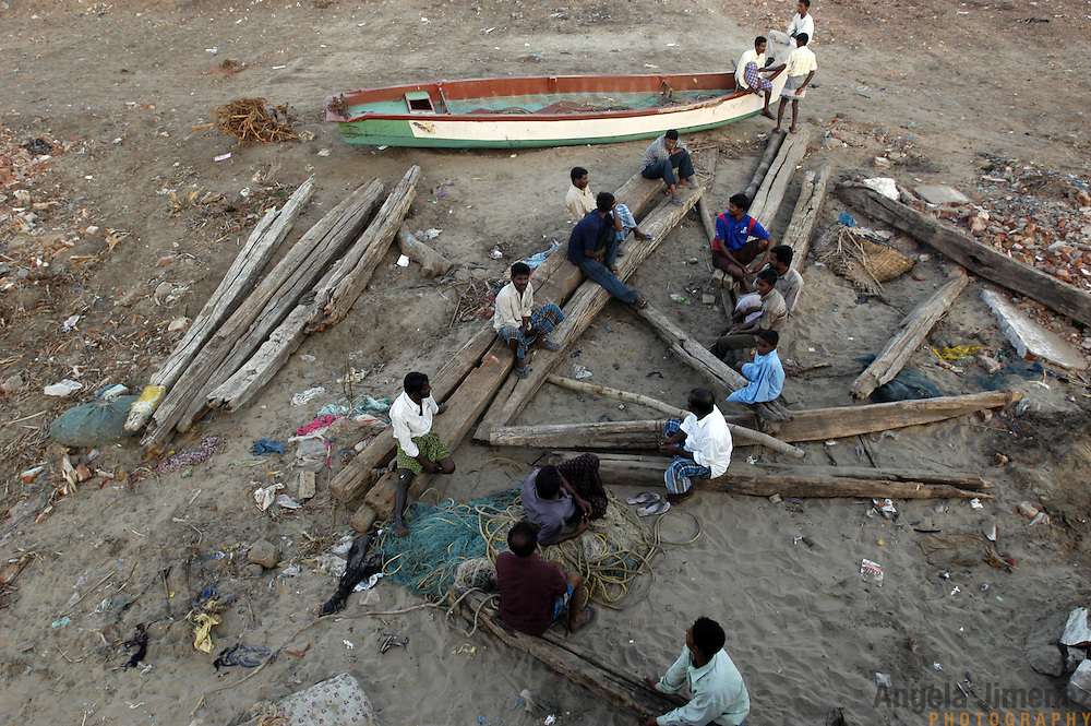 Unemployed fishermen sit on destroyed fishing boats on the beach of Nagapattinam, in Tamil Nadu, India on January 24, 2005, after the area was struck by the Indian Ocean Tsunami on December 26, 2004, destroying nearly all of their fishing boats. Their local union decided to wait for government compensation before making any repairs to their equipment. Generated by an earthquake on the ocean floor, the tsunami devastated the fishing industry along the southeastern coast of India.