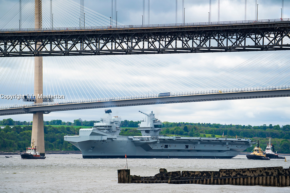 North Queensferry, Scotland, UK. 23 May 2019. Aircraft carrier HMS Queen Elizabeth sails from Rosyth in the River Forth after a visit to her home port for a refit. She returns to sea for Westlant 19 deployment and designed to focus on the operations of her F-35 fighter aircraft. Pictured; Carrier passes underneath Queensferry Crossing Bridge at low tide.