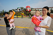 """Tian'anmen Square (Place of Heavenly Peace). Flower display with Beijing 2008 Olympics mascots (""""Friendlies"""") from left: Jingjing, the panda, fiery Huanhuan. Chinese one-child families taking souvenir photos."""