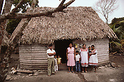 A family in front of their thatched roof home in a Mayan village, Yucatan, Mexico.