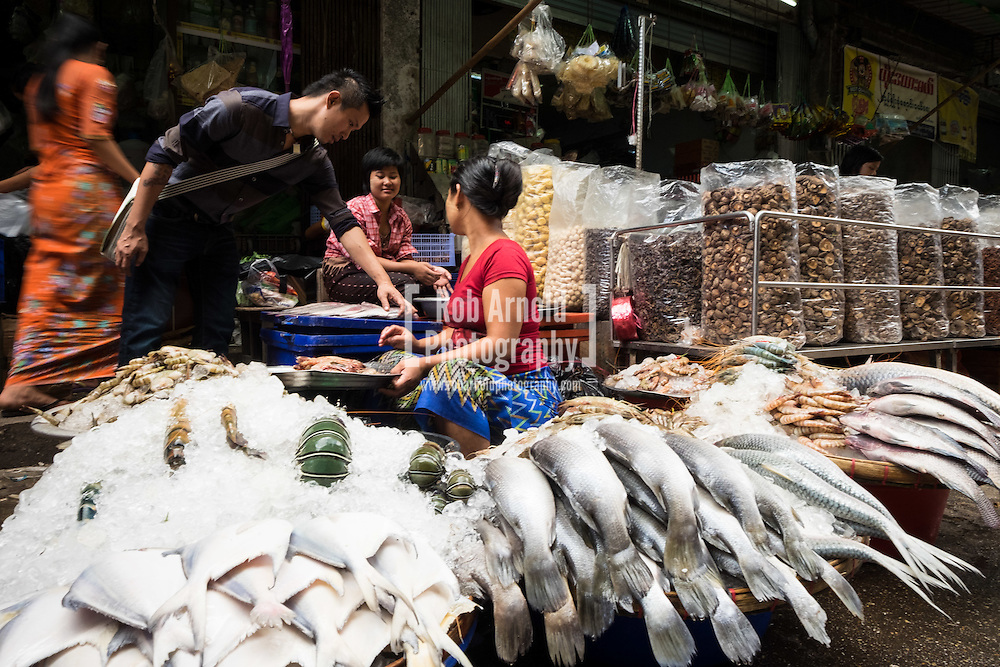 Women selling fresh fish at their street market stall in Downtown Yangon.
