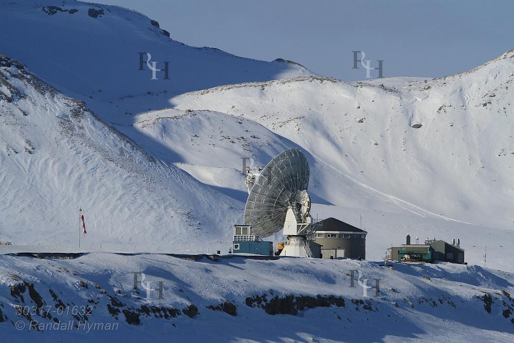 Snowy mountains dwarf VLBI radio telescope at Hamarabben Airport above the international science village of Ny-Alesund on Spitsbergen island in Kongsfjorden; Svalbard, Norway.