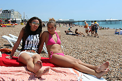 © Licensed to London News Pictures.21/06/2014. Brighton, UK. Two woman sunbathing on Brighton Beach. Thousands of people are taking a weekend away to the South Coast with temperatures reaching 25C. Photo credit : Hugo Michiels/LNP