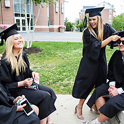 Margaret Silverman of Brunswick, Maine, Delaney Nalen of Denver, Colo., watch as Kathleen Denoia of Falmouth, Maine, adjusts Jack Maritz cap while waiting along Alumni Walk at the start of Commencement on May 27, 2018.