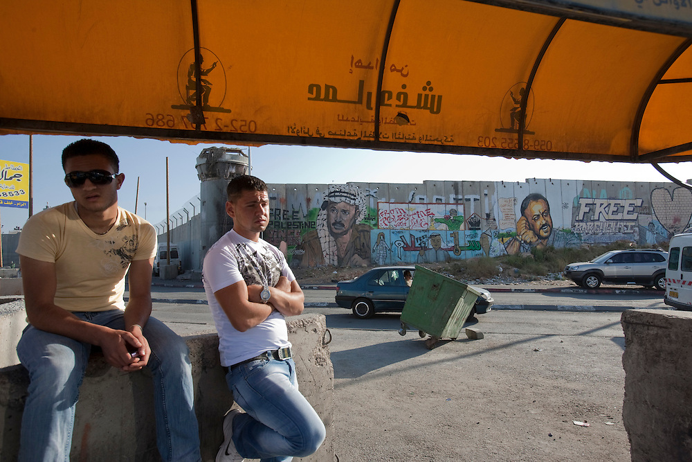 Young Palestinian men wait for a cab at Qualandia checkpoint as he is seen in the back a graffiti of Yasser Arafat and Marwan Barghouti two of the main political figures in Ramaalah on June 06, 2011. Photo by Olivier Fitoussi