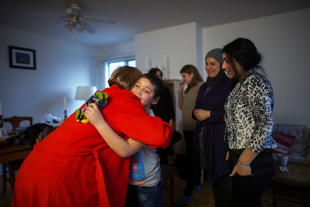 Syrian refugee Nasimi Batal Al Hasan is hugged by sponsor Valerie Pringle as his sister Rania Batal (right) looks on inside their apartment in Mississauga, Ontario, Canada, Thursday January 21, 2016.   (Mark Blinch for the BBC)