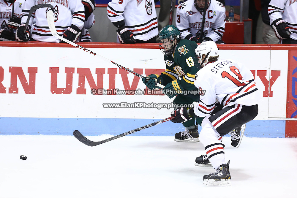 Dan Senkbeil #13 of the Vermont Catamounts and John Stevens #18 of the Northeastern Huskies fight for the puck during the game at Matthews Arena on January 18, 2014 in Boston, Massachusetts. (Photo by Elan Kawesch)