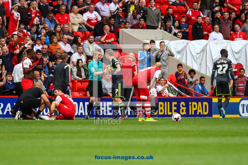 Albert Adomah of Middlesbrough (right) leaves the field after being sent off for a challenge on Rhoys Wiggins of Charlton Athletic (2nd left) who receives treatment for his injury during the Sky Bet Championship match at The Valley, London<br /> Picture by David Horn/Focus Images Ltd +44 7545 970036<br /> 27/09/2014
