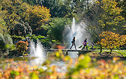 © Licensed to London News Pictures. 27/10/2014. Cliveden, UK. People cross over stepping stones to the Chinese water garden.  People walk through the autumnal trees in the morning sunshine at Cliveden House in  Buckinghamshire. Today 27th October 2014. Photo credit : Stephen Simpson/LNP